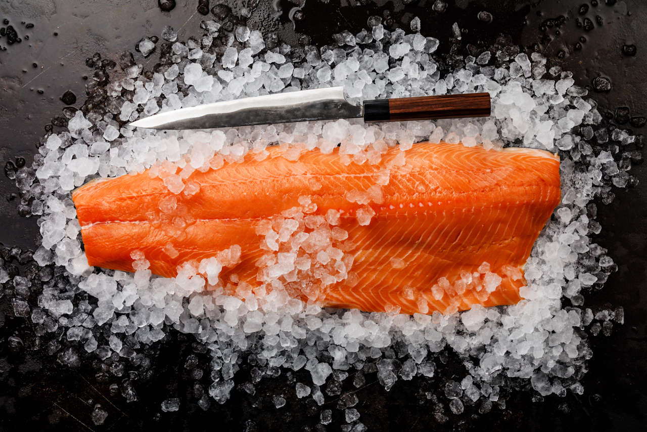 A large side of salmon with filleting knife