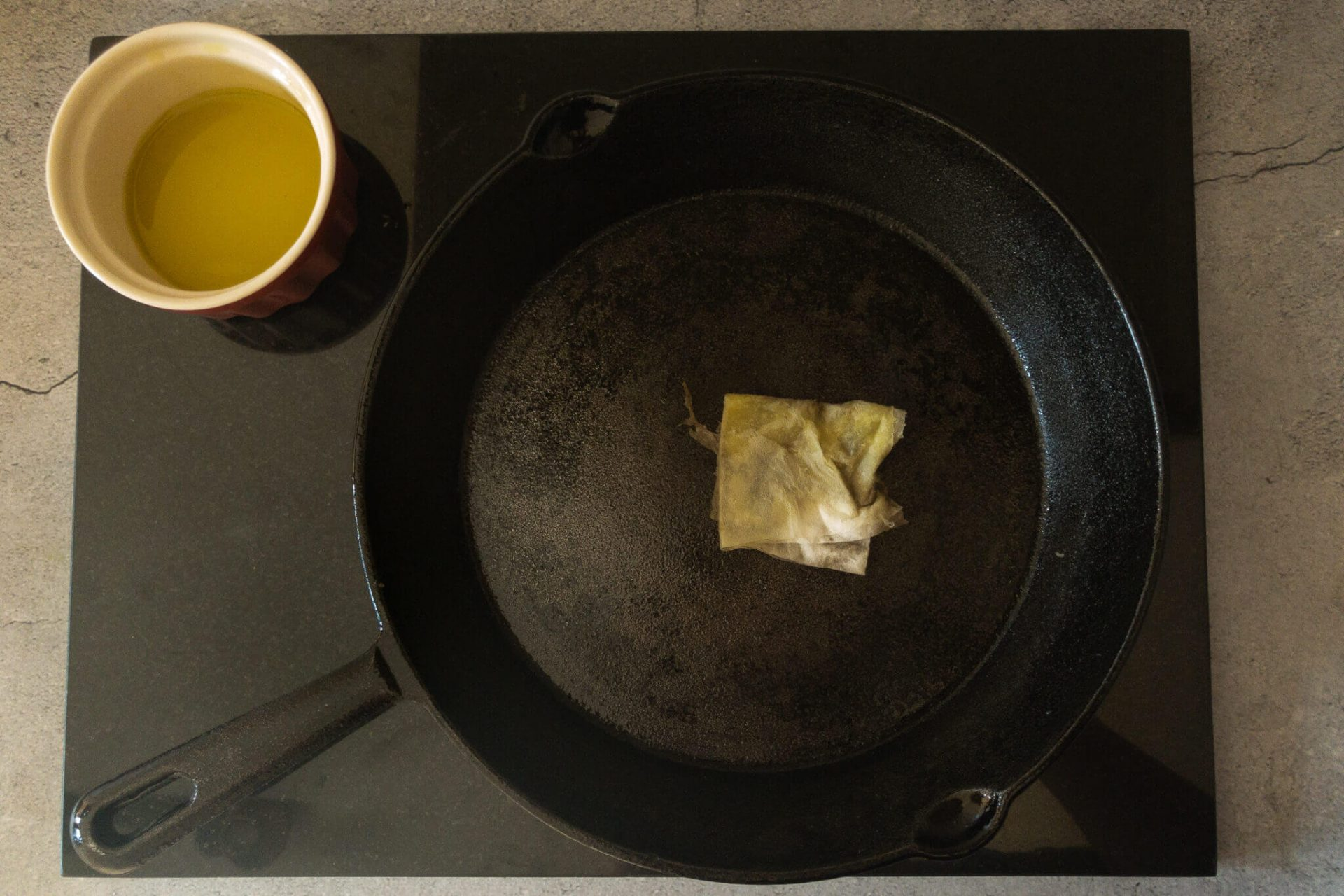 Using a cotton pad to apply a thing layer of oil onto the skillet