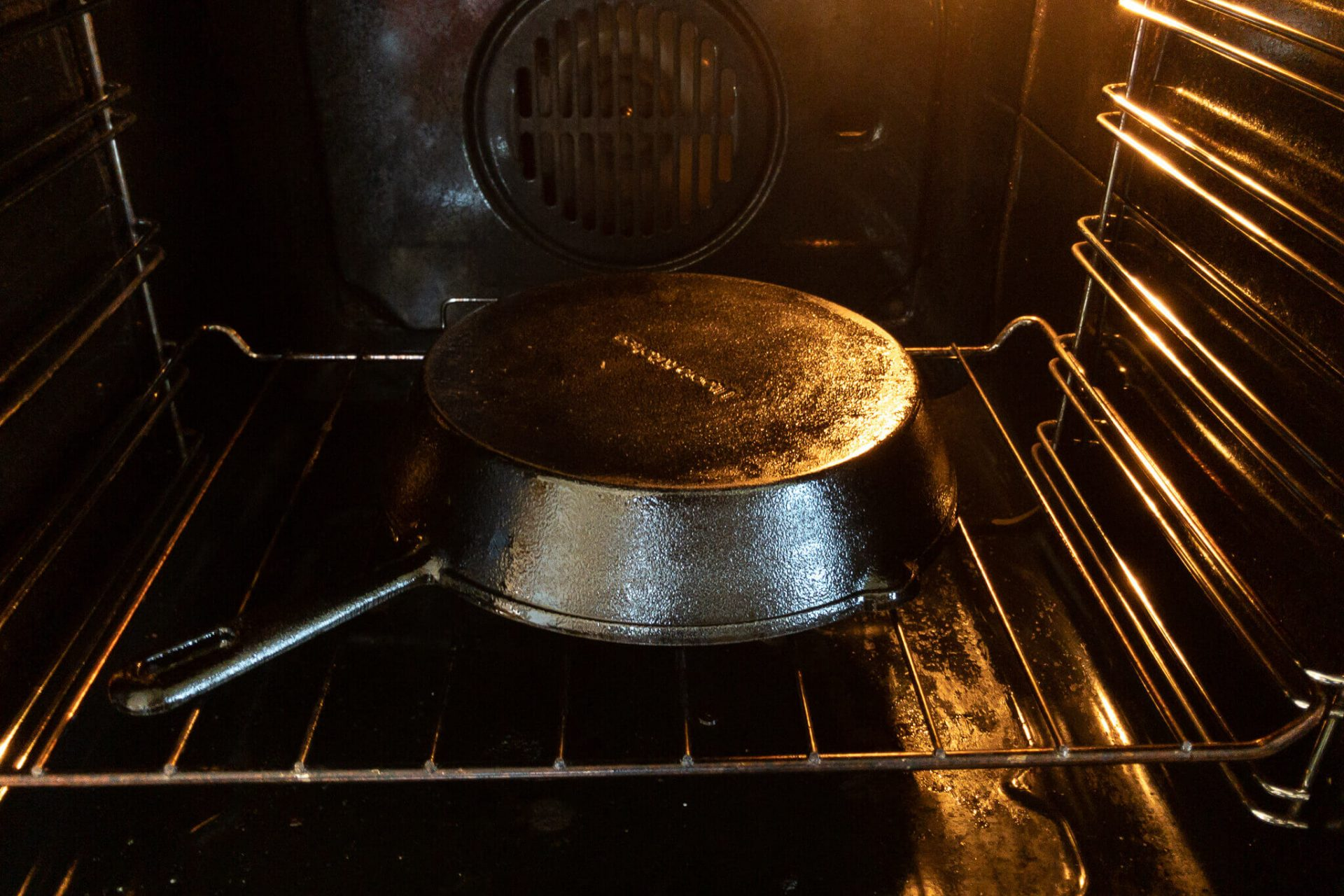 A freshly seasoned cast iron skillet ready to bake in a hot oven.