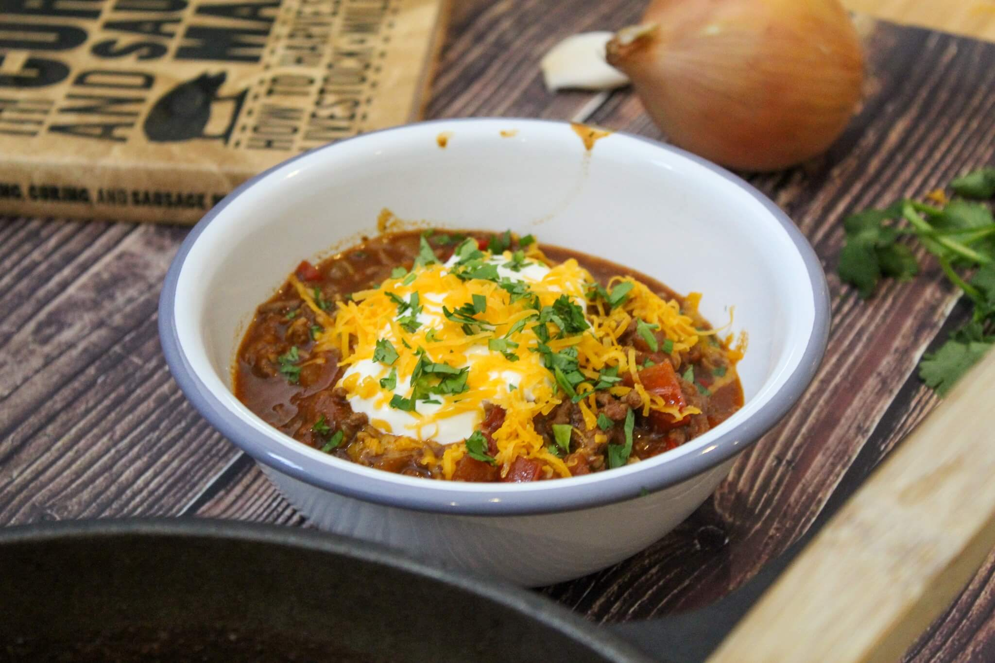 Freshly cooked texan chili with sour cream, cheese, and cilantro