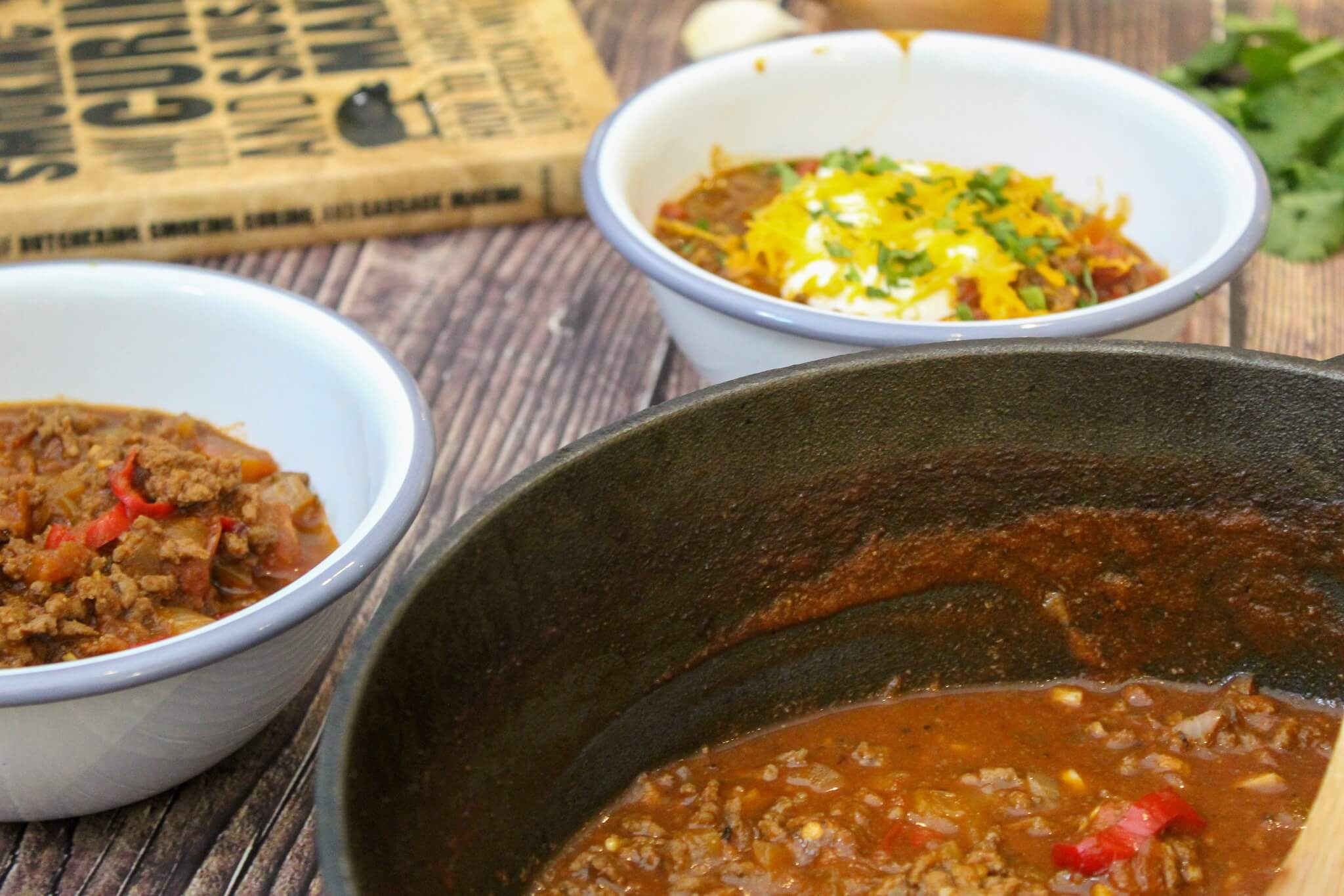 Chili in two bowls and a skillet