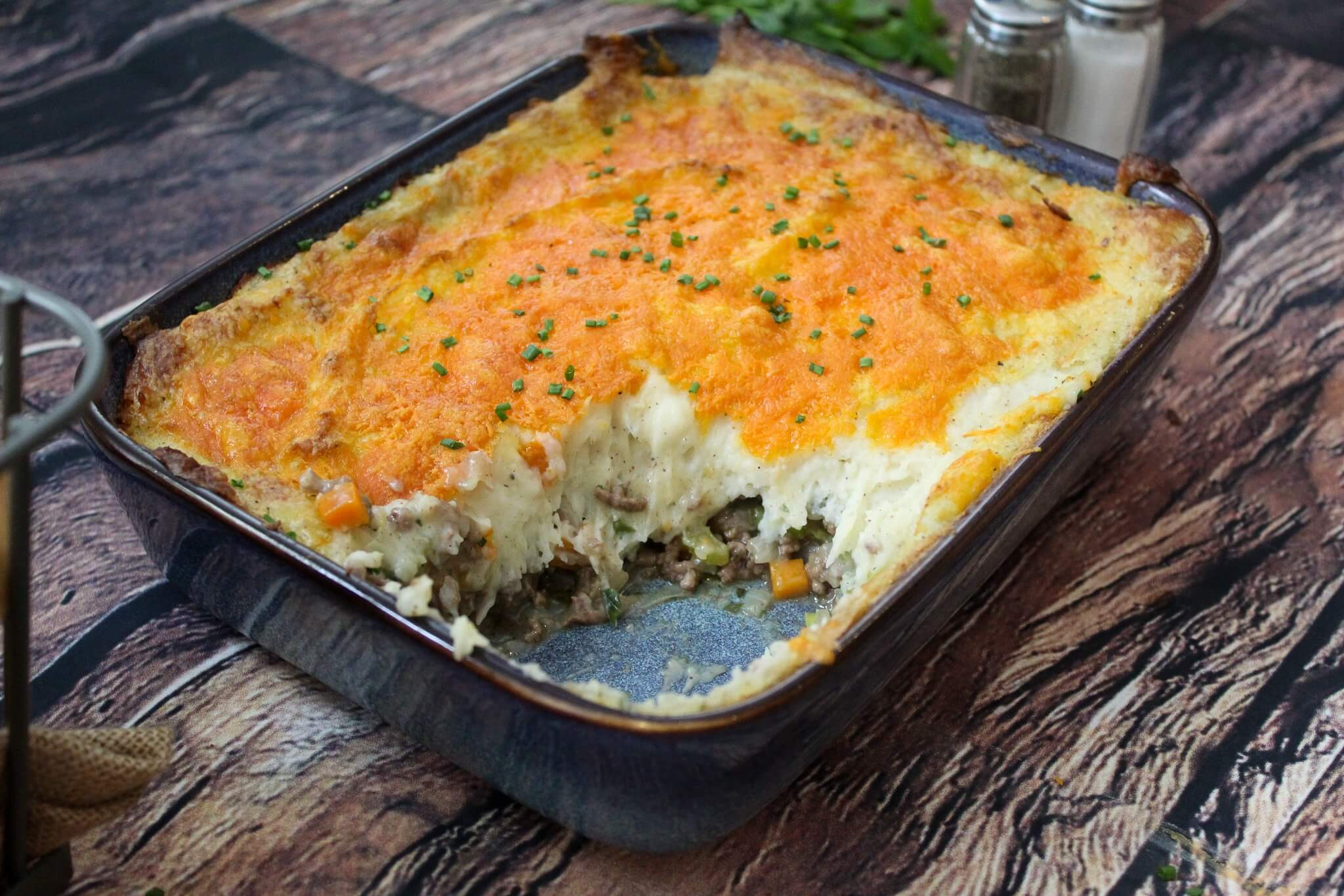 Cottage pie with a slice take out of it exposing the filling