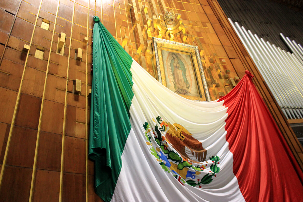 A famous painting of Virgin de Guadalupe hung over a large Mexican flag
