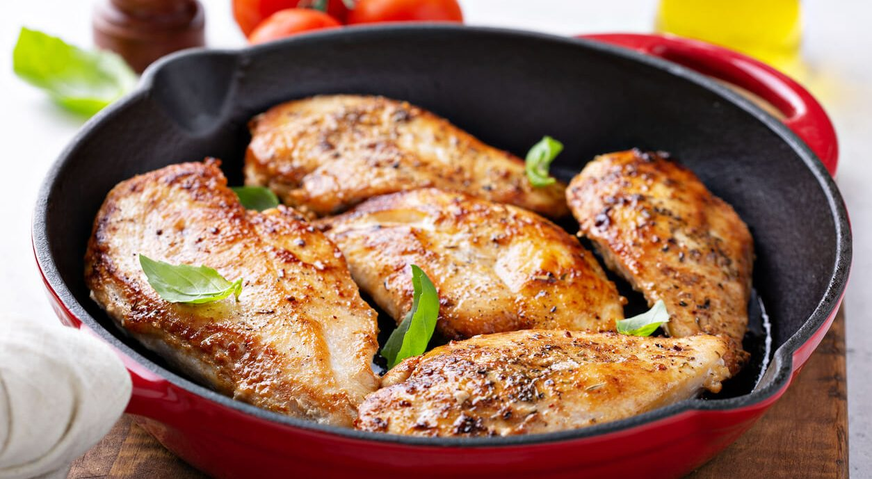 Oven baked chicken breasts in a skillet