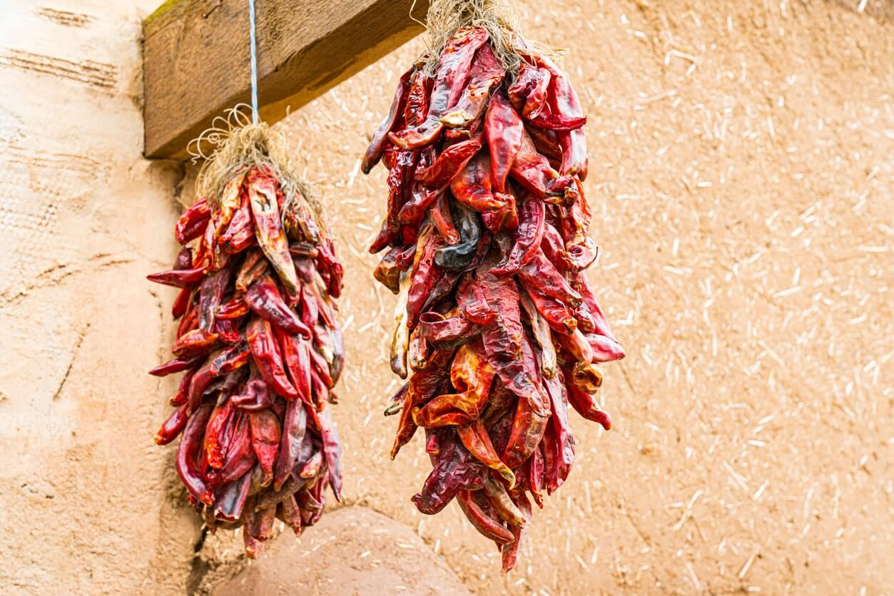 dried chillies hanging from a wooden post